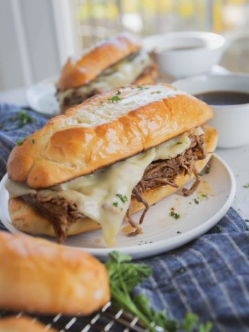 A French dip sandwich on a white plate. The sandwich is toasted and the cheese is melted over the meat. Another sandwich is in the background, and a hoagie roll is next to the sandwich.