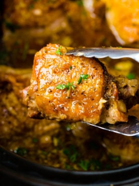 A photo of one perfectly cooked chicken thigh being held up by metal tongs from our slow cooker garlic chicken recipe.