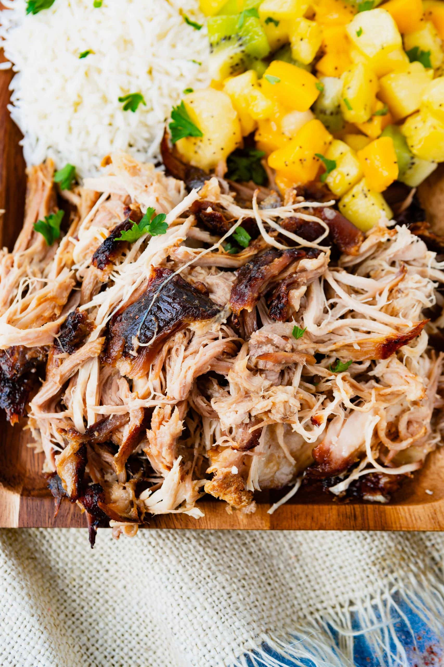 a photo of tender, juicy kalua pulled pork on a wooden serving platter