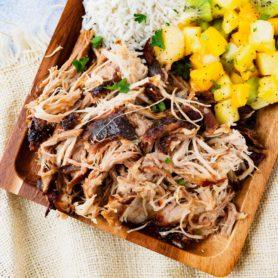 a photo of a rectangular wooden platter full of kalua pulled pork, herbed rice, tropical fruit salad and golden Hawaiian rolls.