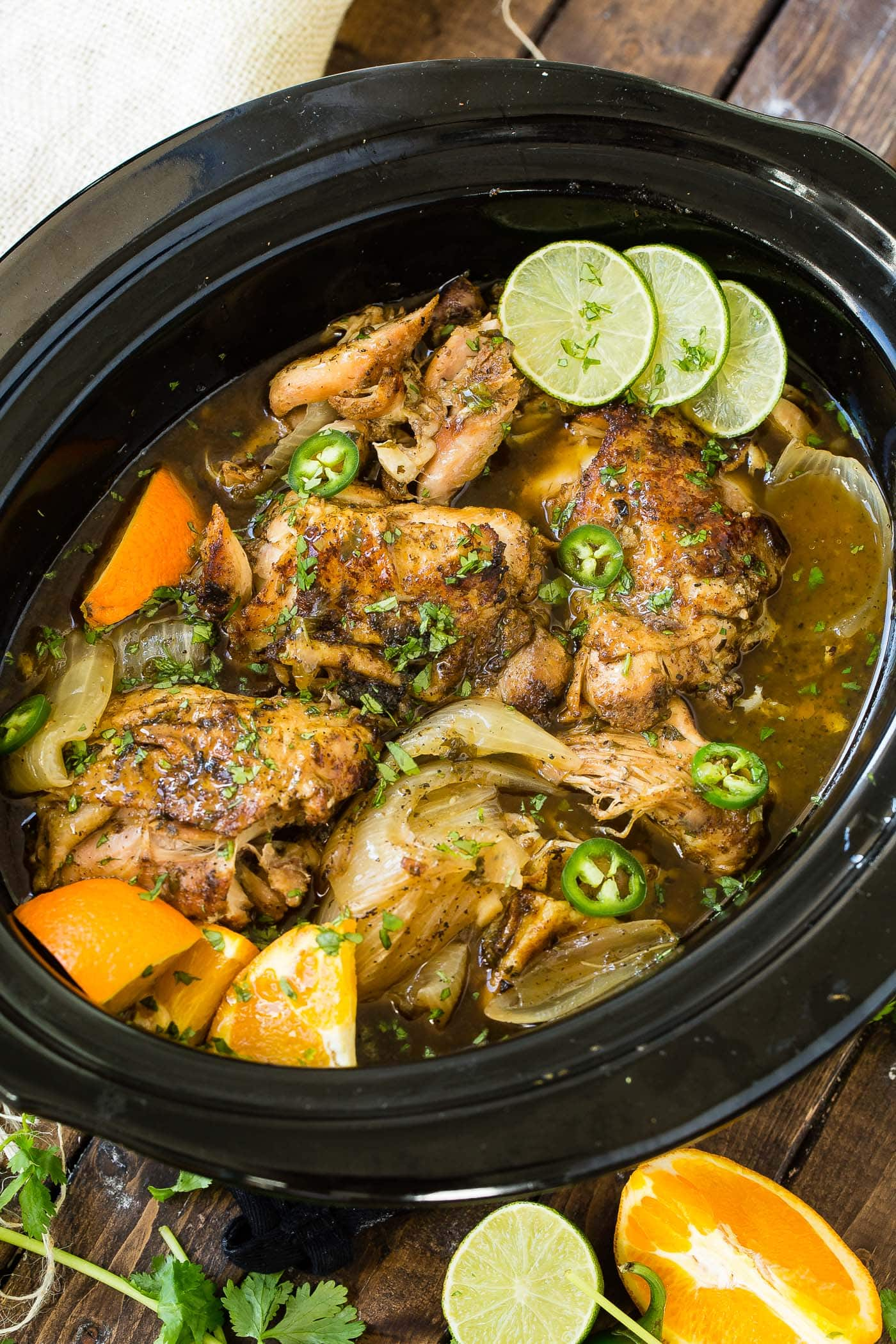 A photo of chicken carnitas being cooked in a slow cooker witl slices of fresh lime.