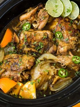 A photo of chicken carnitas being cooked in a slow cooker.