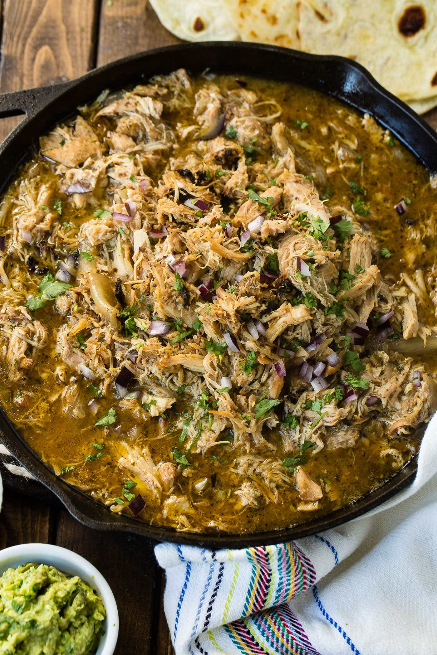 A photo of juicy crispy chicken carnitas in a cast iron skillet garnished with chopped cilantro and diced red onion.