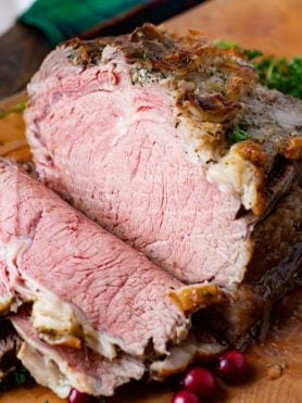A photo of slow cooker prime rib half sliced on a cutting board