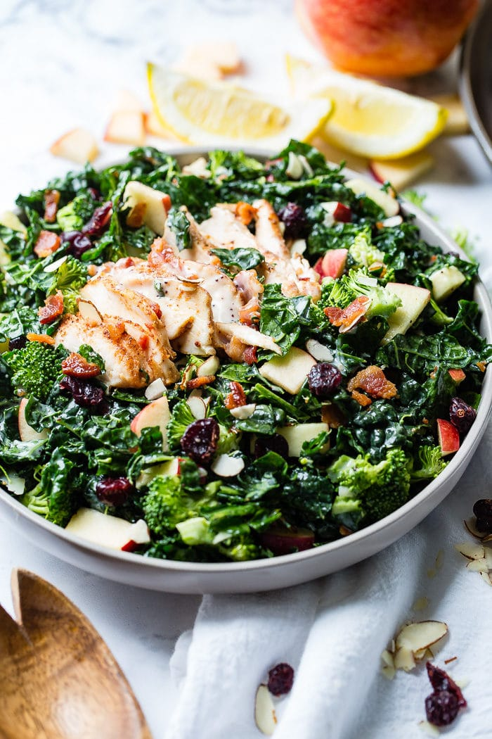 A photo of a kale salad loaded with apples, bacon, cranberries and smoked chicken.
