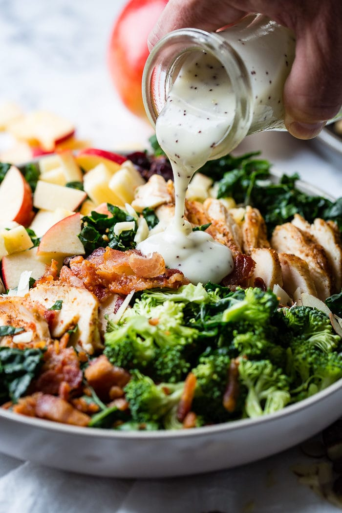 A photo of a kale salad loaded with apples, bacon, cranberries and smoked chicken topped with poppy seed dressing being poured on top.