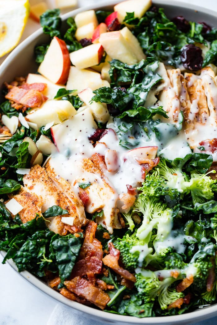 A photo of a kale salad loaded with apples, bacon, cranberries and smoked chicken topped with a poppy seed dressing.