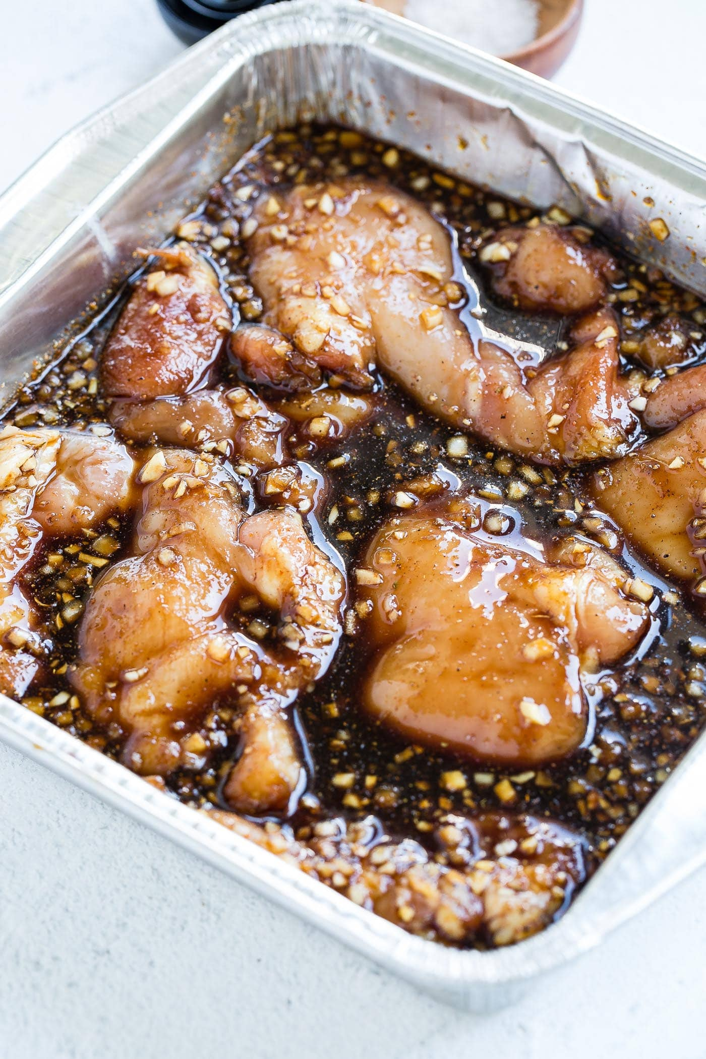 A large dish with chicken thighs marinating in a dark brown sauce.