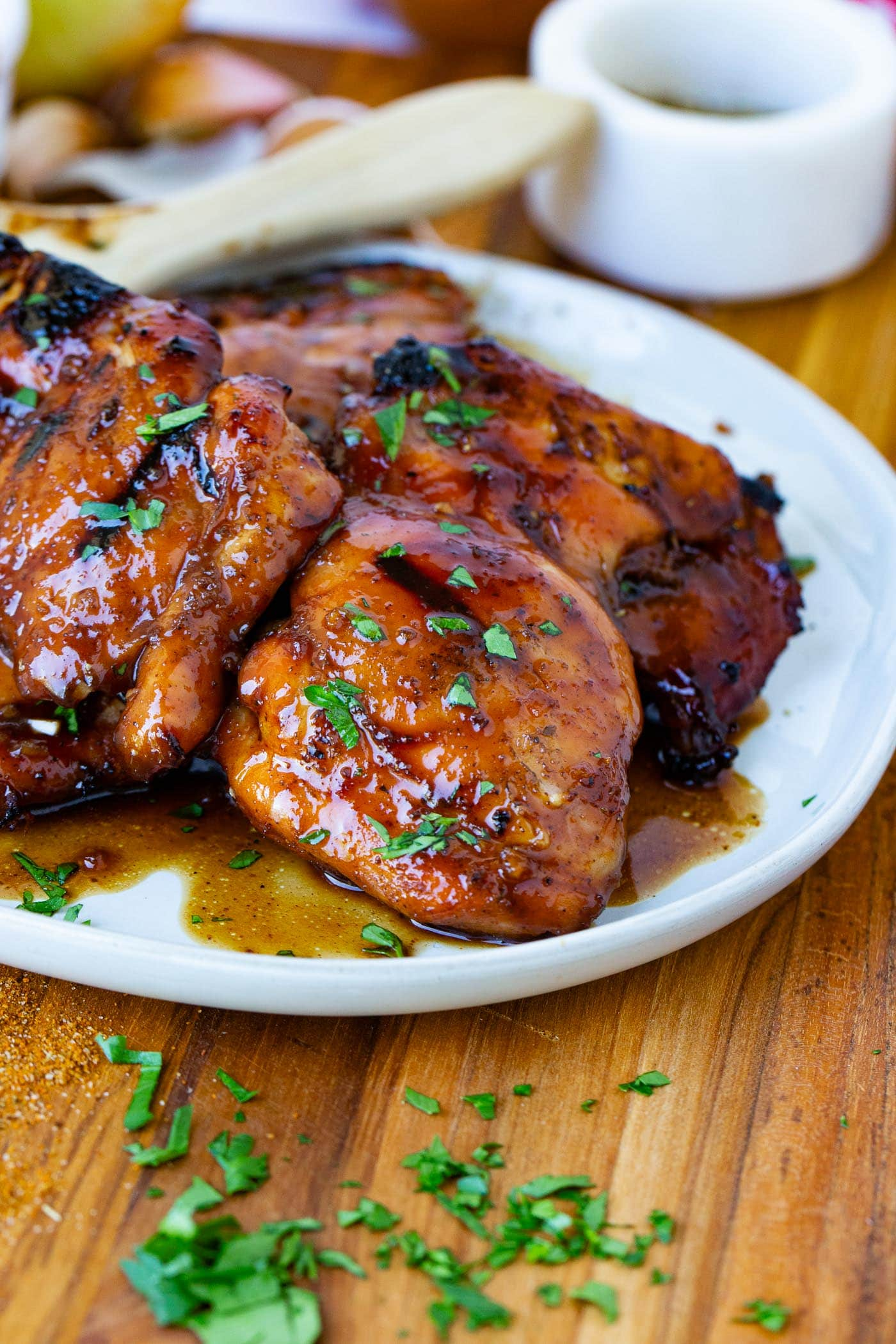 A serving plate of marinated smoked chicken thighs sprinkled with fresh green herbs.