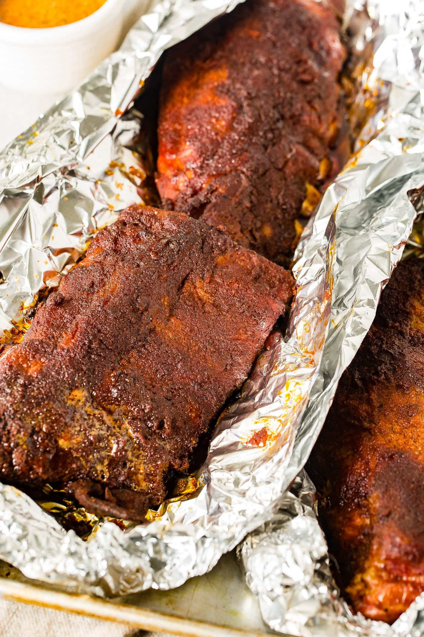 A photo of smoked ribs hot off the smoker still wrapped in foil with the foil just opened on the top.