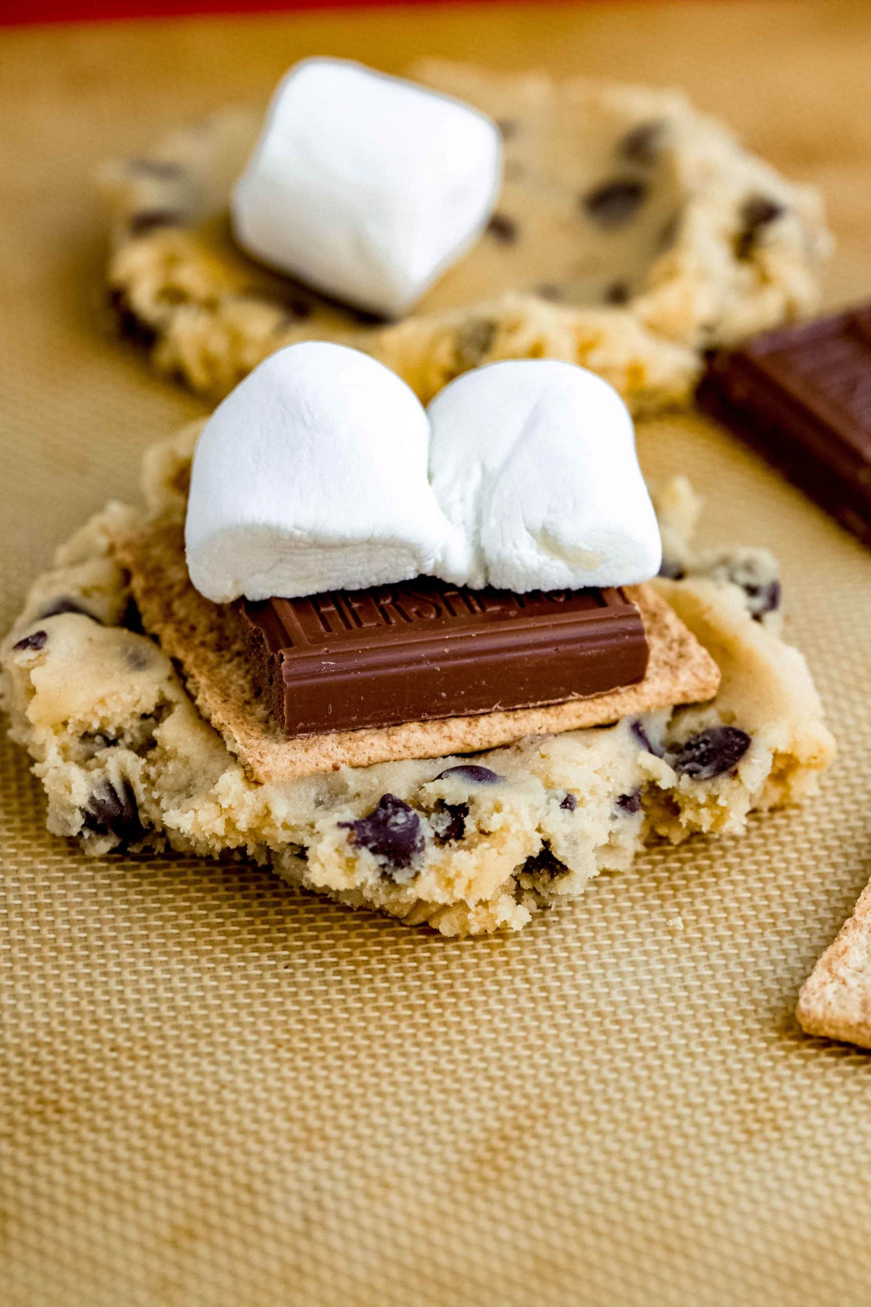 A baked chocolate chip cookie with a graham cracker, chocolate bar, and marshmallow on top. Another cookie and marshmallow are in the background.