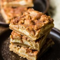 Snickerdoodle cookie dough crust, a cheesecake filling and more snickerdoodle cookies on top for the most fantastic snickerdoodle cheesecake bars ever