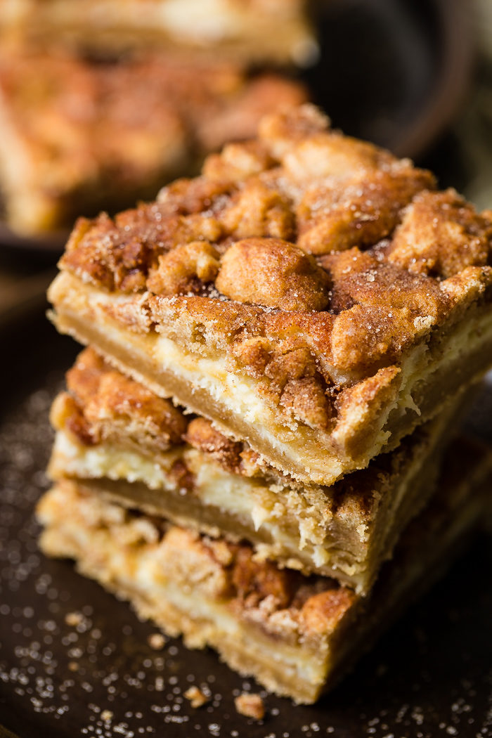 three snickerdoodle cheesecake bars stacked on top of each other