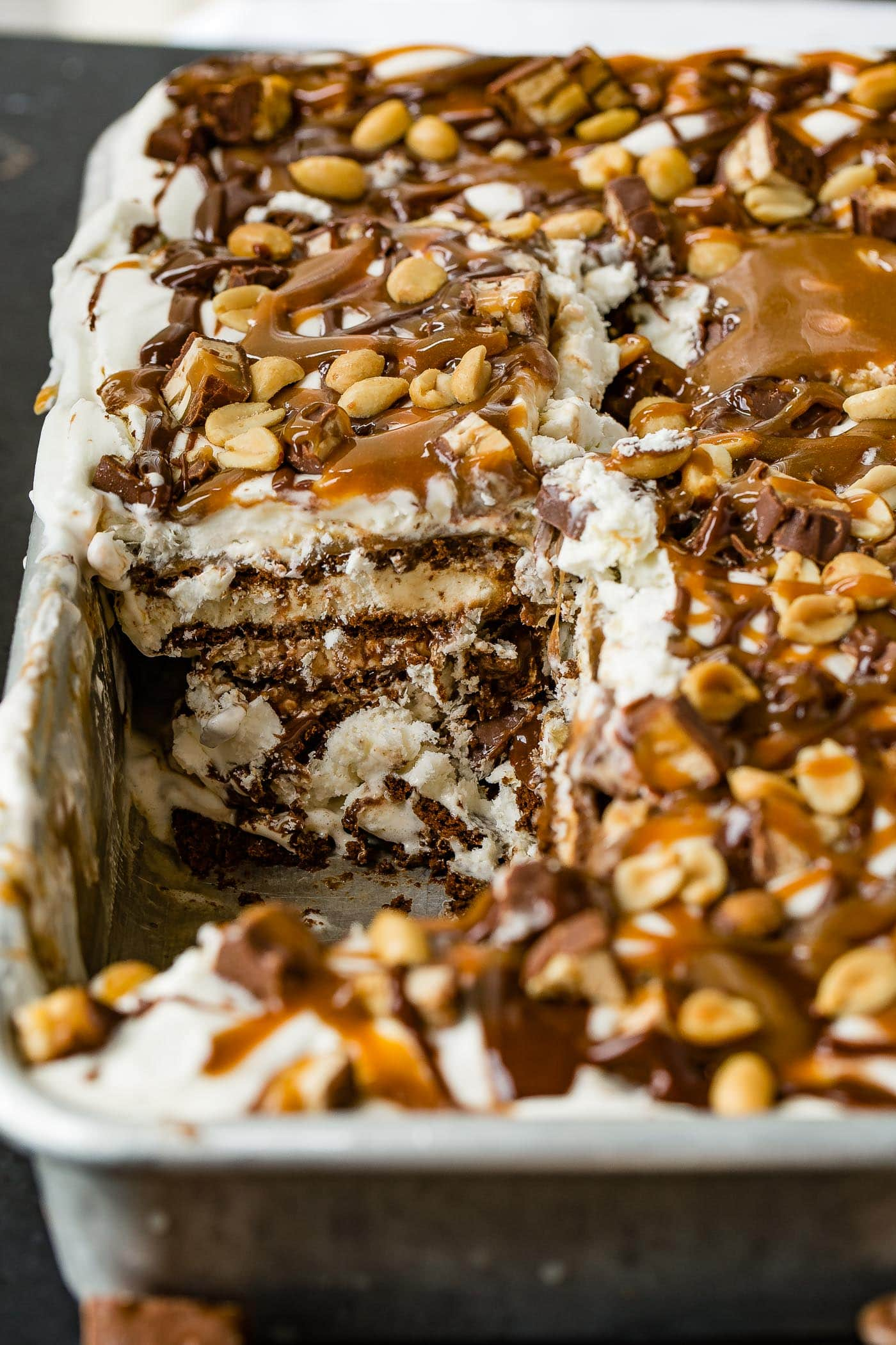A pan of snickers ice cream cake with a piece removed. There are layers of ice cream, cake, fudge, caramel, whipped cream and candy bars. The top is drizzled with hot fudge, caramel topping and salted peanuts.