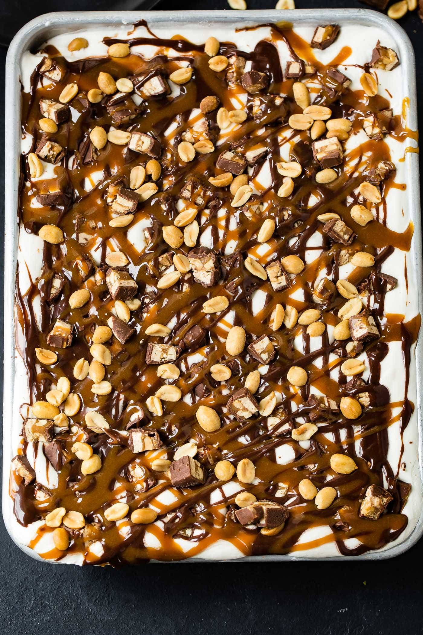 A pan of snickers ice cream cake. The top is covered with whipped cream, hot fudge, drizzles of caramel sauce, chopped snickers bars and salted peanuts