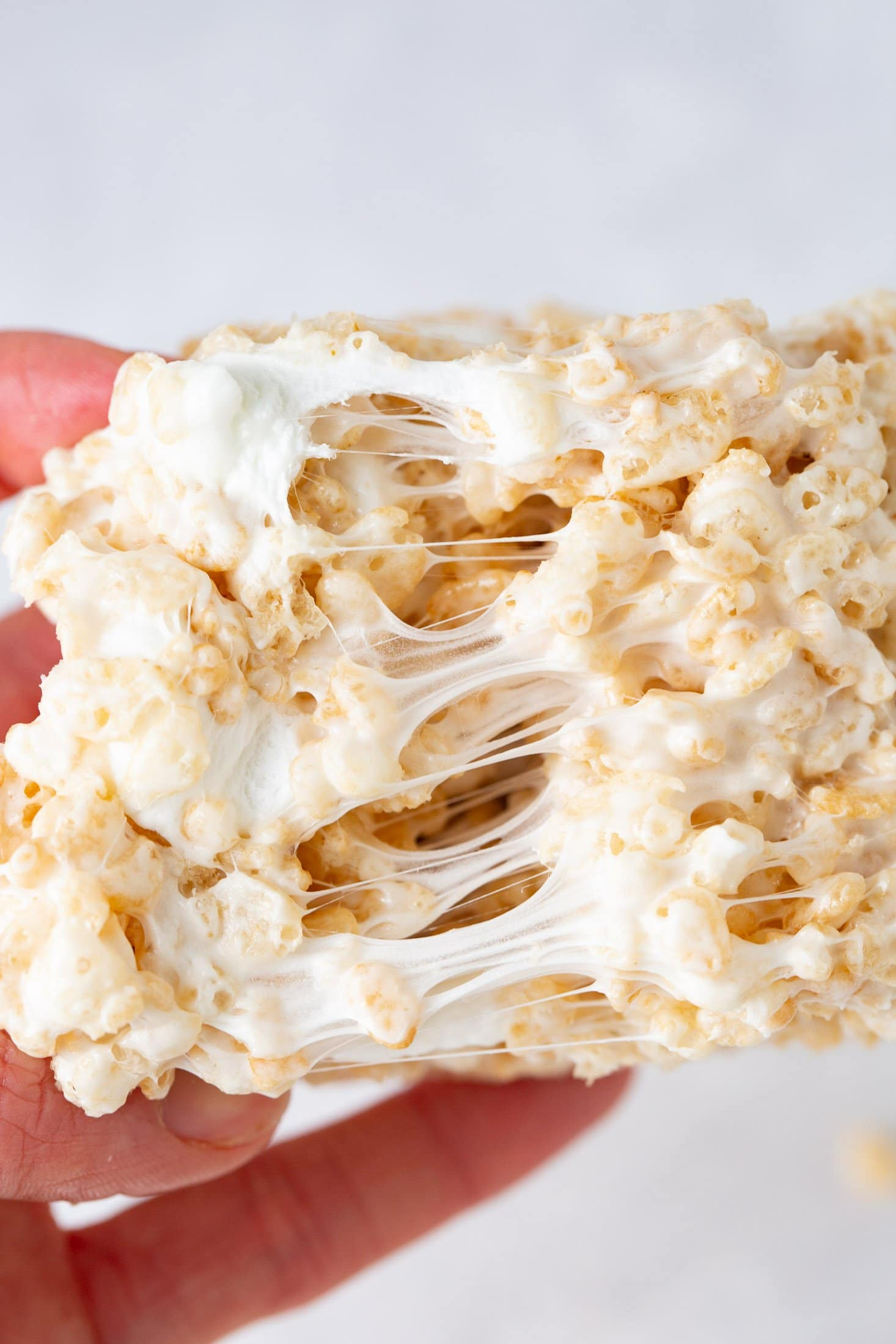A piece of rice krispie treat that is being pulled apart to show the gooey melted marshmallow holding the rice krispies together.