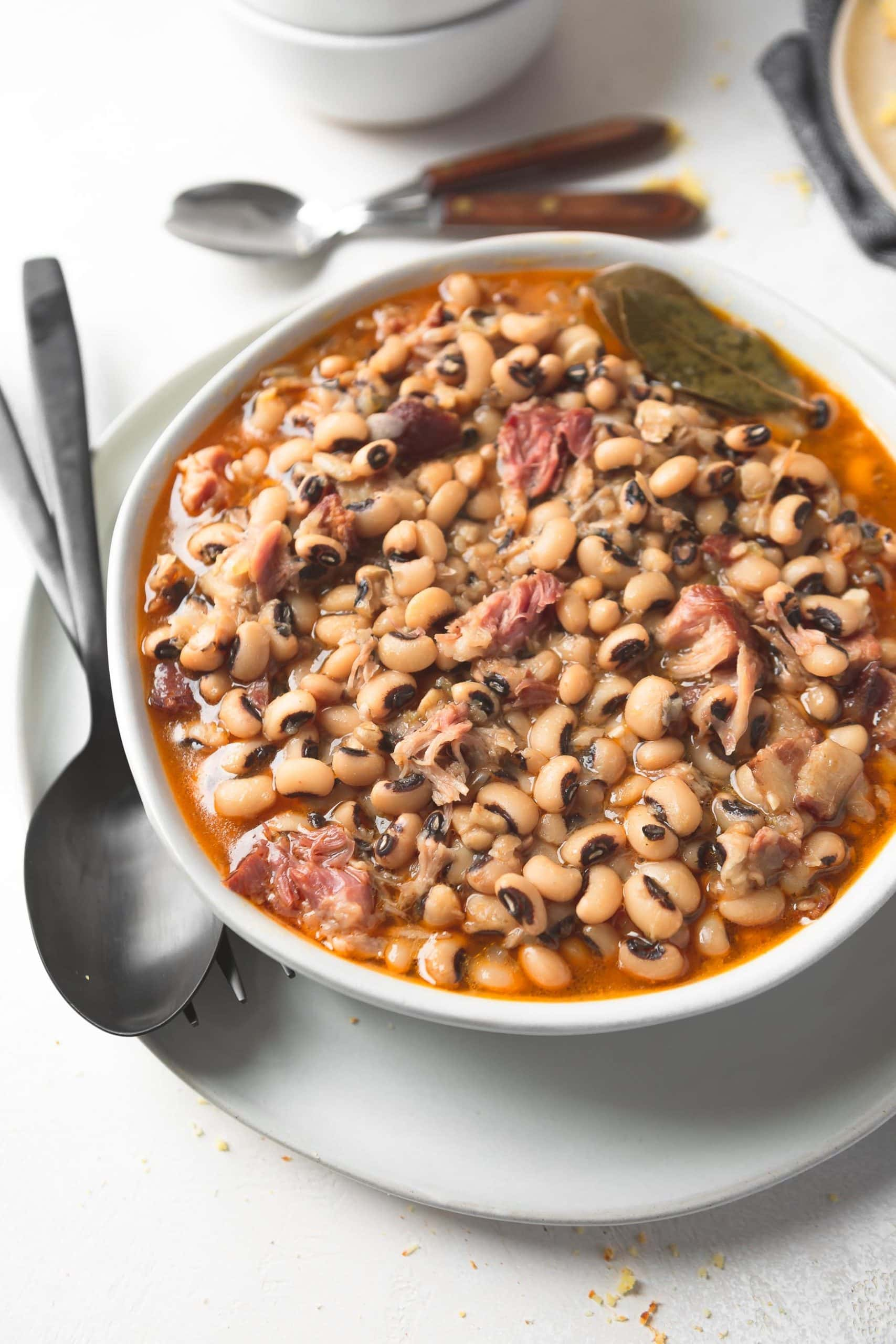 A bowl of southern black eyed peas. A spoon and fork are sitting next to the bowl.