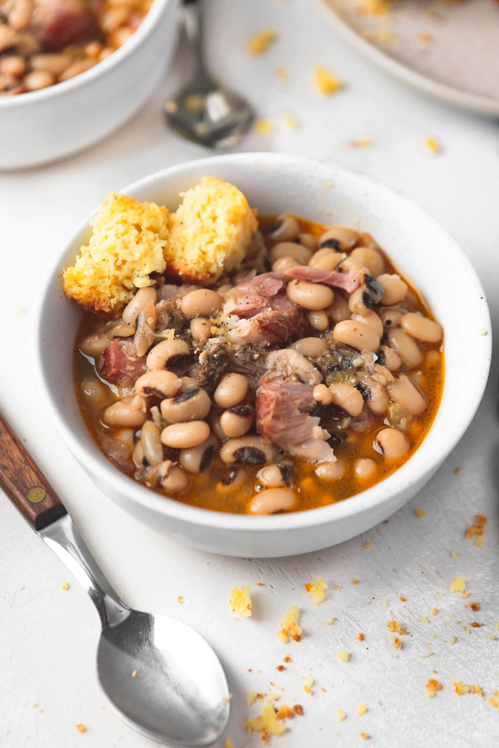 A bowl of southern black eyed peas. There are chunks of ham in the peas and a broken piece of cornbread on the side.