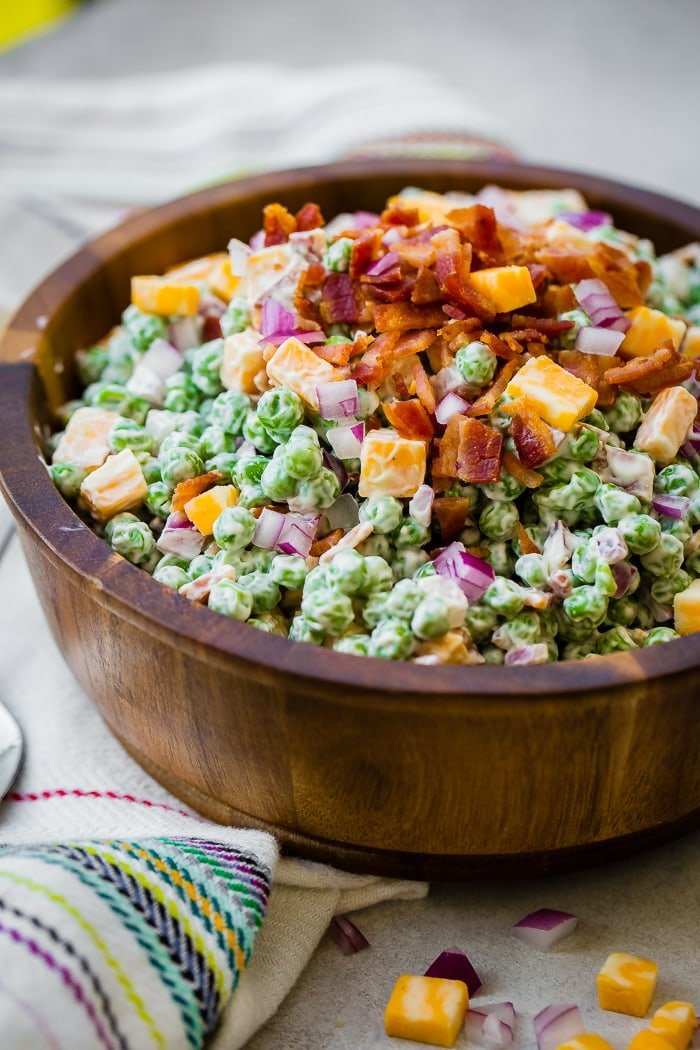 a wooden bowl full of creamy southern english pea salad with bacon, chunks of colby jack cheese