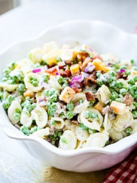 A white bowl with orchiette pasta, peas, cubed colby jack cheese, red onion and a simple dressing for the recipe southern pea pasta salad