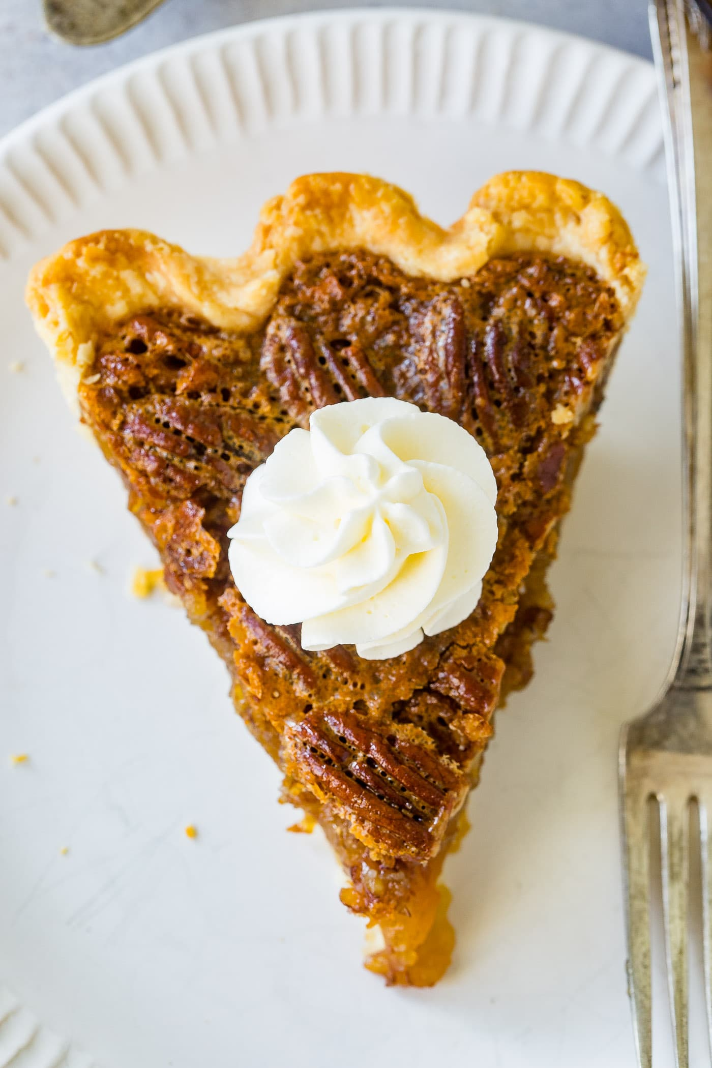 A photo of a slice of pecan pie taken from overhead.