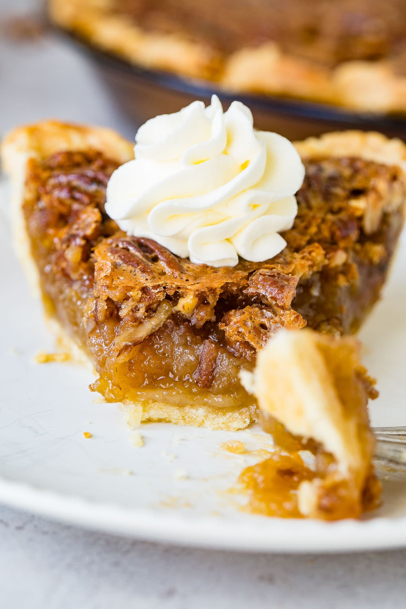 A photo of a slice of pecan pie with a bite taken out.