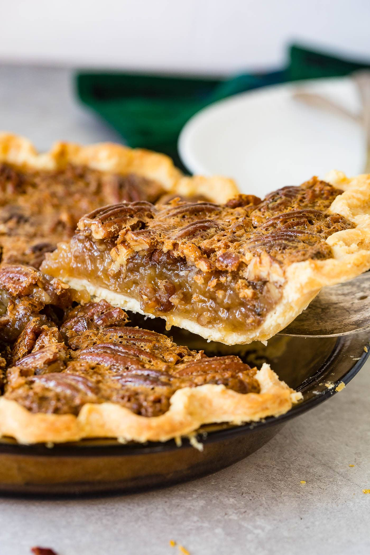 A photo of a slice of pecan pie being removed from a whole pie.