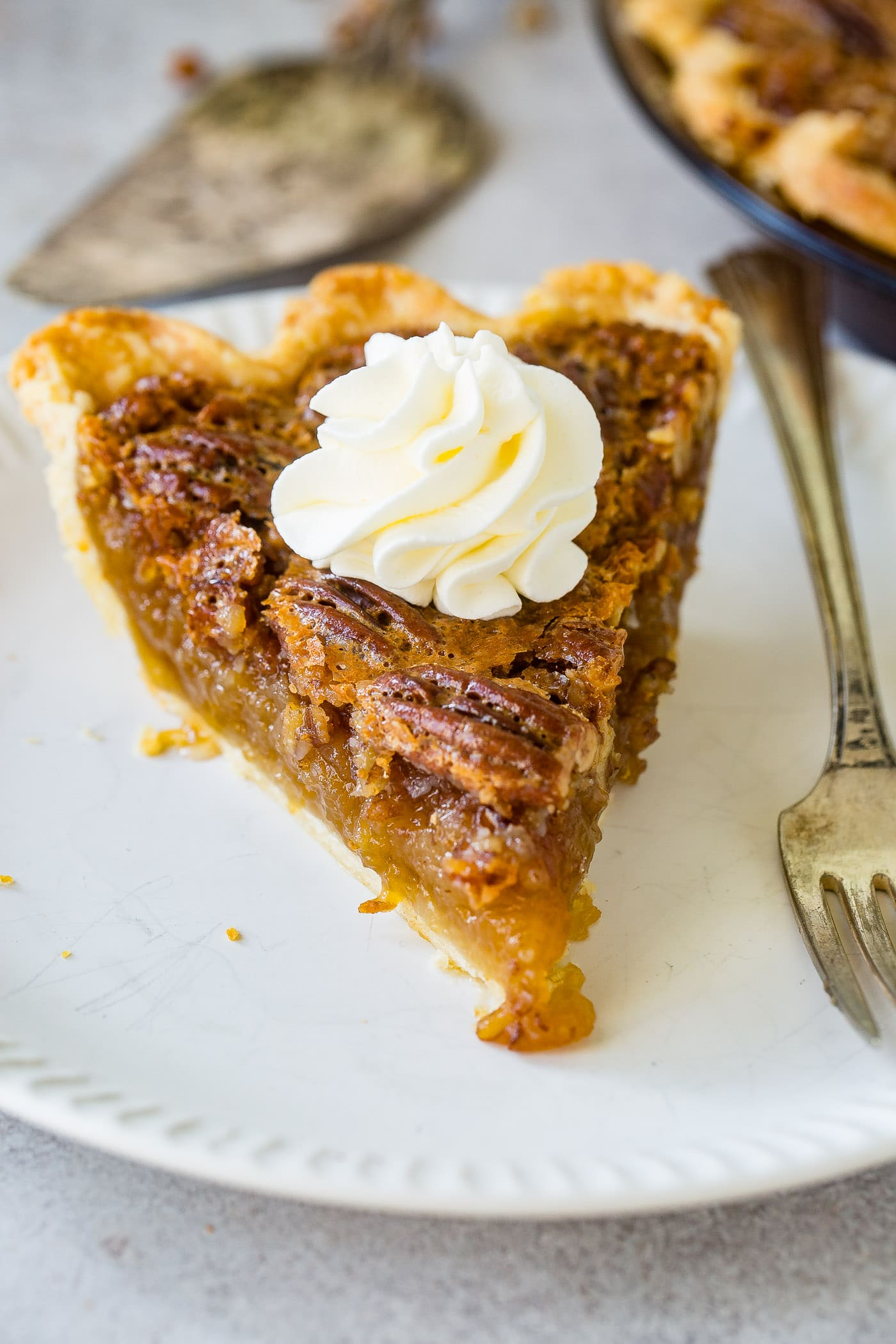 A photo of a slice of pecan pie on a white plate with a fork sitting next to it.