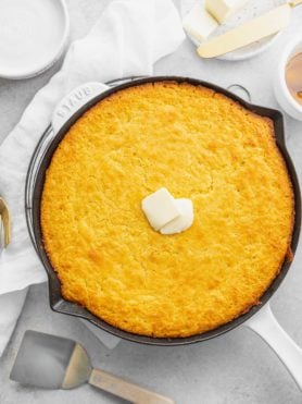 A cast iron skillet with baked cornbread. Two little cubes of butter are in the center of the cornbread.