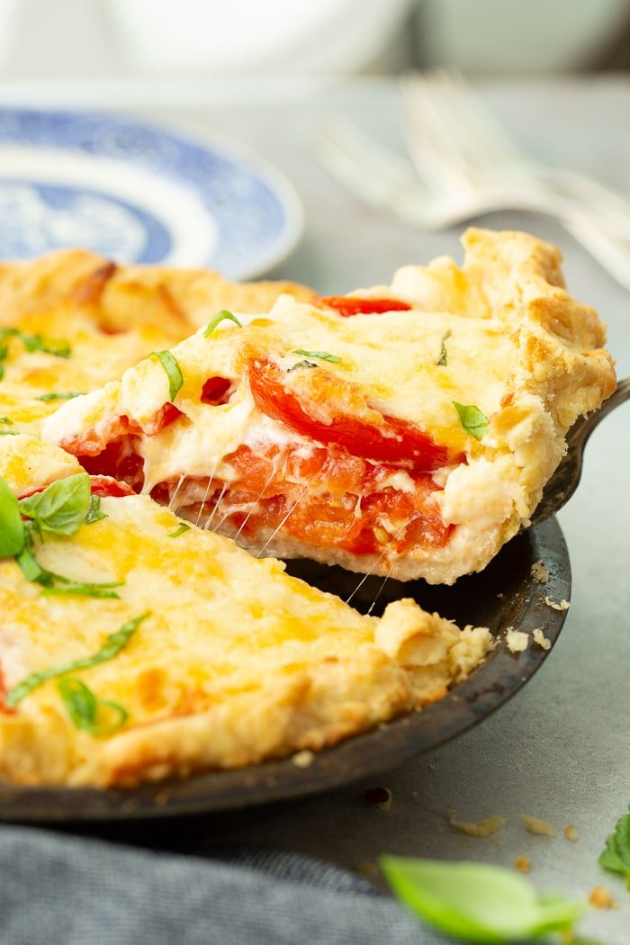a slice of southern tomato pie on a blue china plate