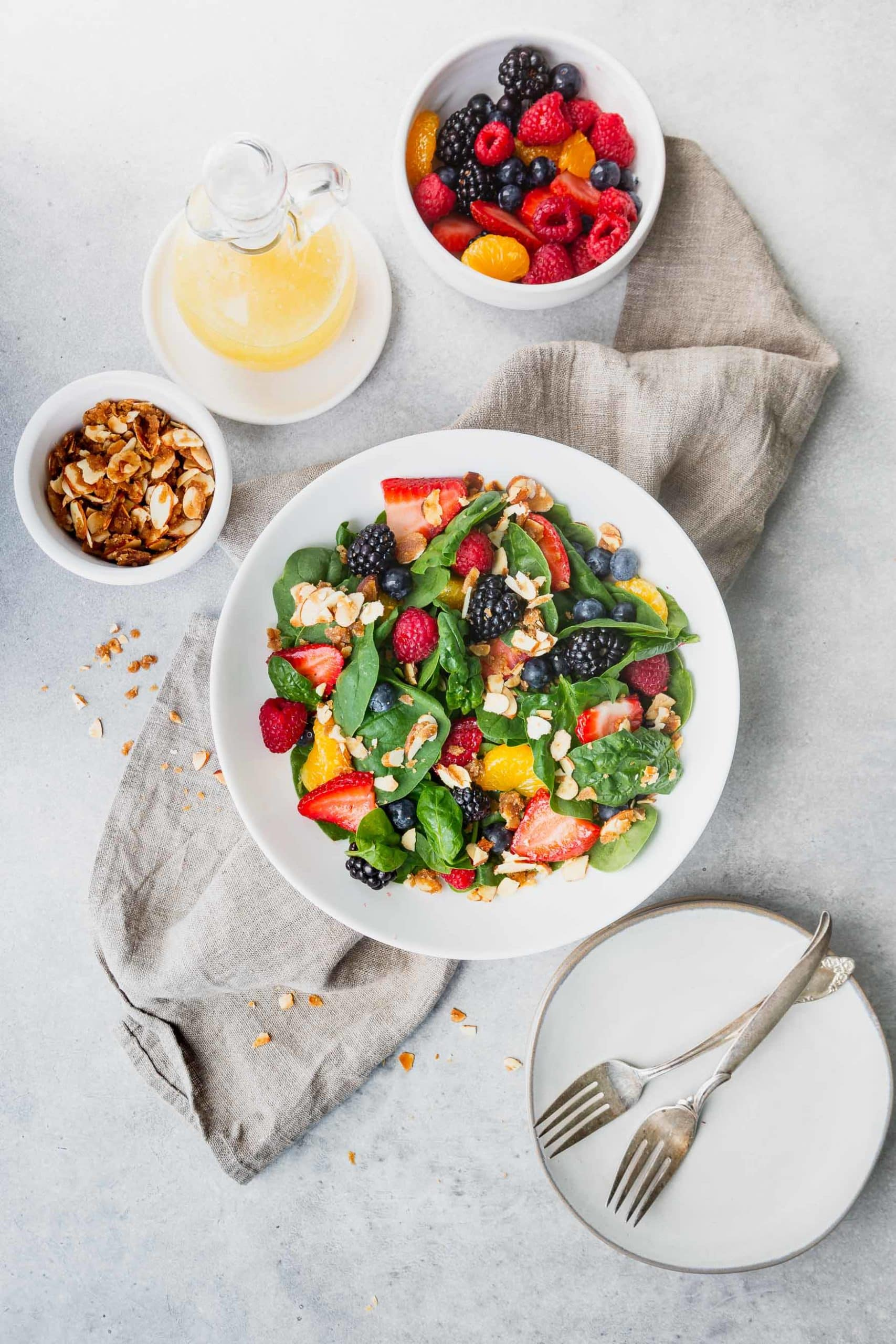 a photo of a large white ceramic bowl full of spinach berry salad with a bowl of brown sugar almonds next to it, a small salad plate with two forks crossing on it, a bottle of lemon dressing and a bowl full of fresh berries.
