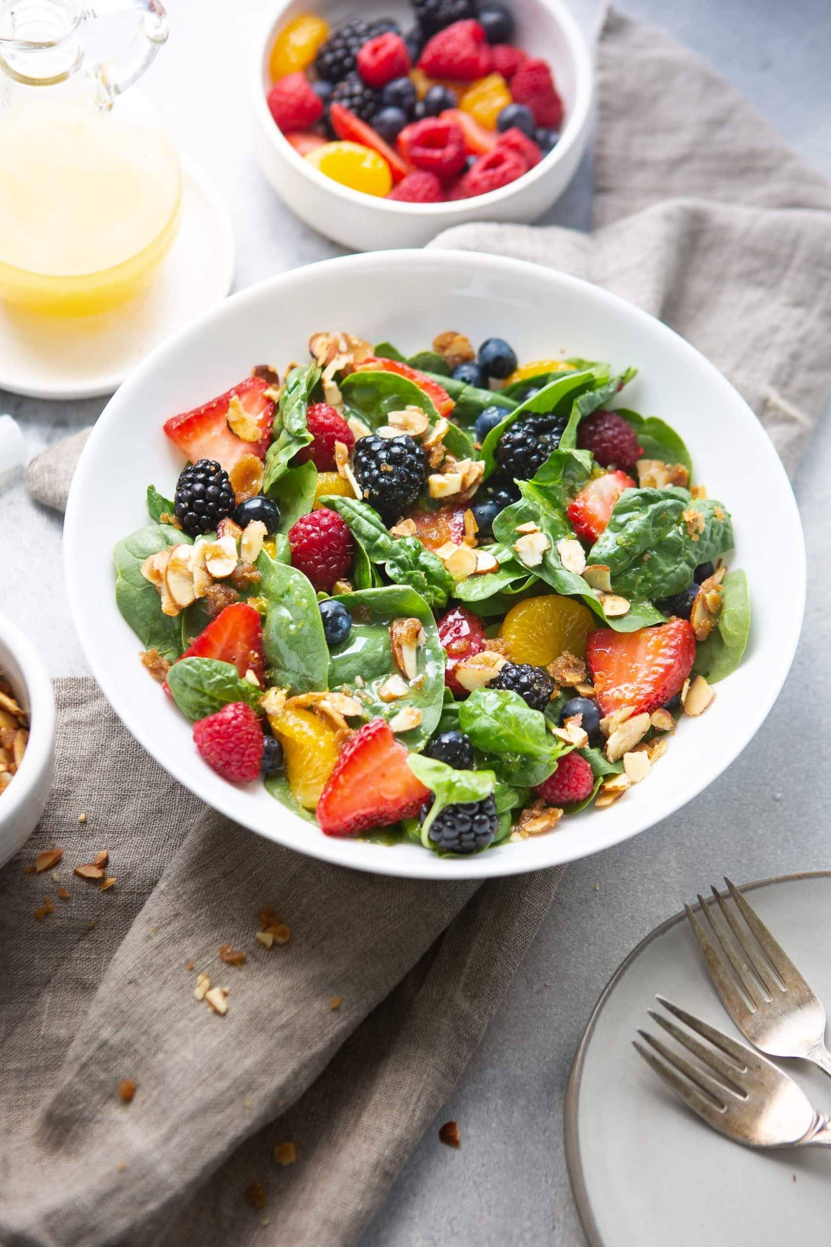 a photo of spinach berry salad in a large white ceramic bowl.