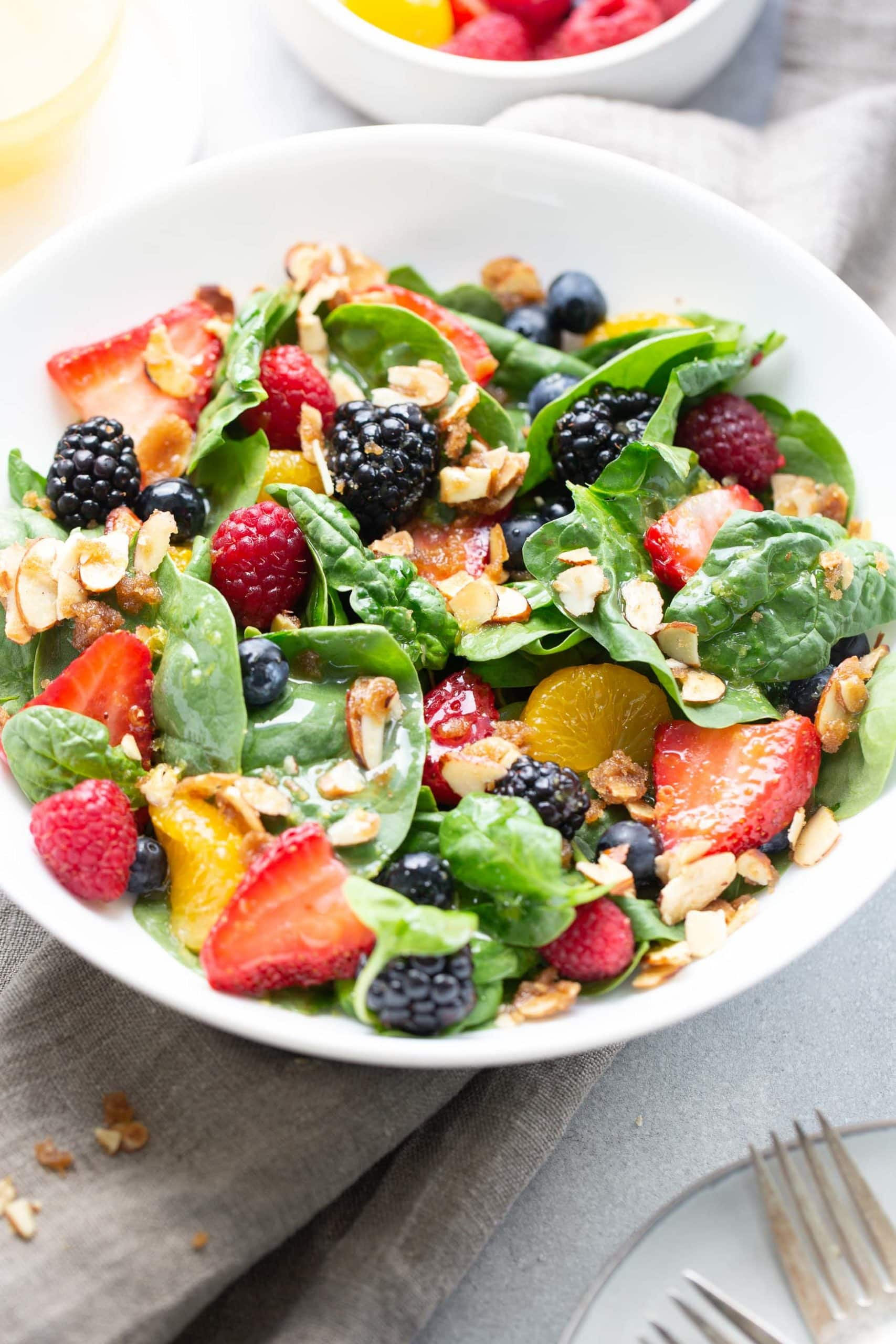 A photo of a large ceramic white bowl full of spinach berry salad topped with brown sugar almonds and blackberries, raspberries, and strawberries.