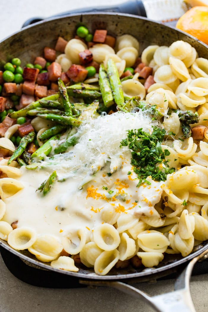 A photo of a skillet pan full of the ingredients for ham and asparagus lemon cream sauce unmixed.