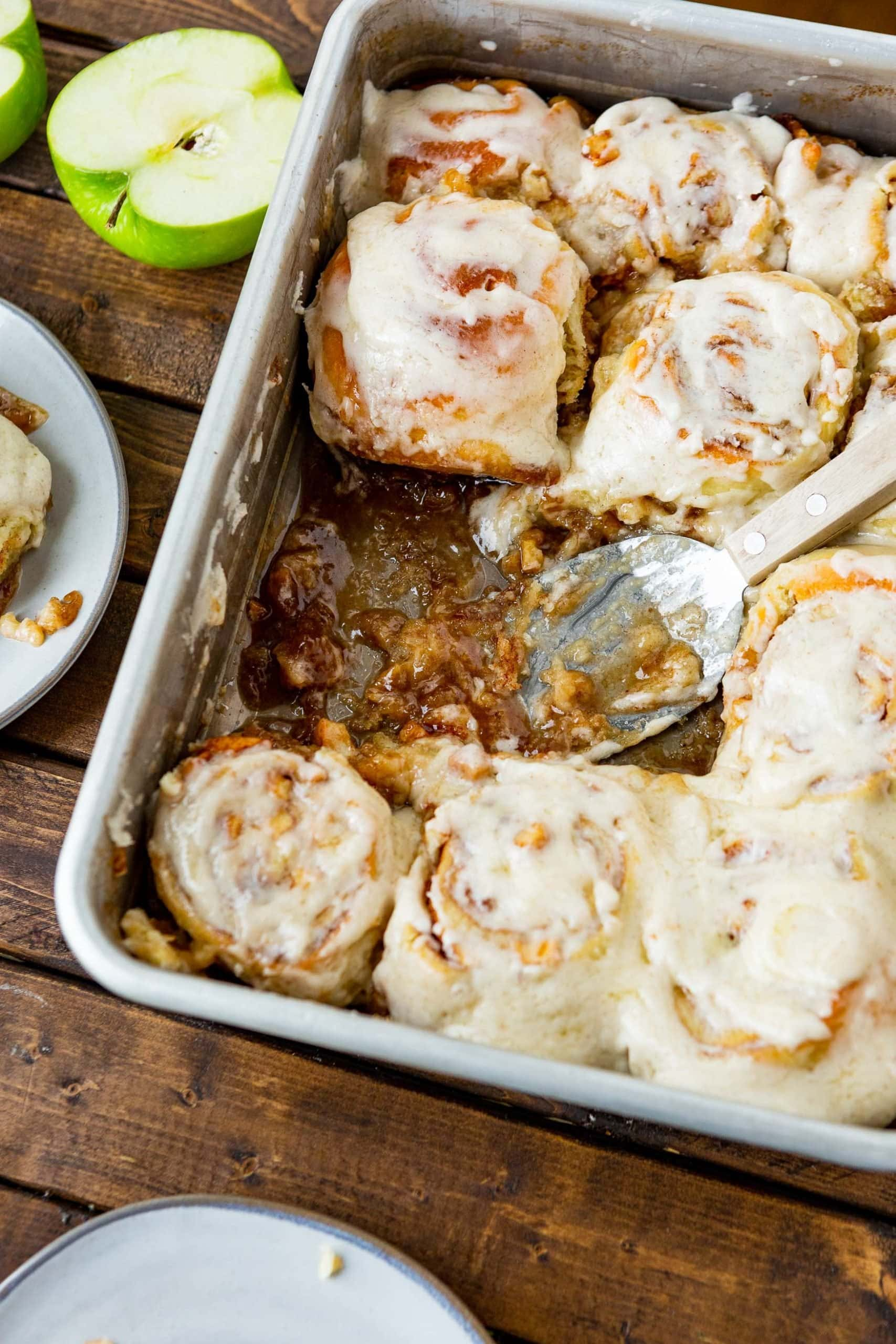 a photo of a 9x13 metal pan full of frosted golden cinnamon rolls with two cinnamon rolls missing and a serving spatula sitting in their place in the pan.