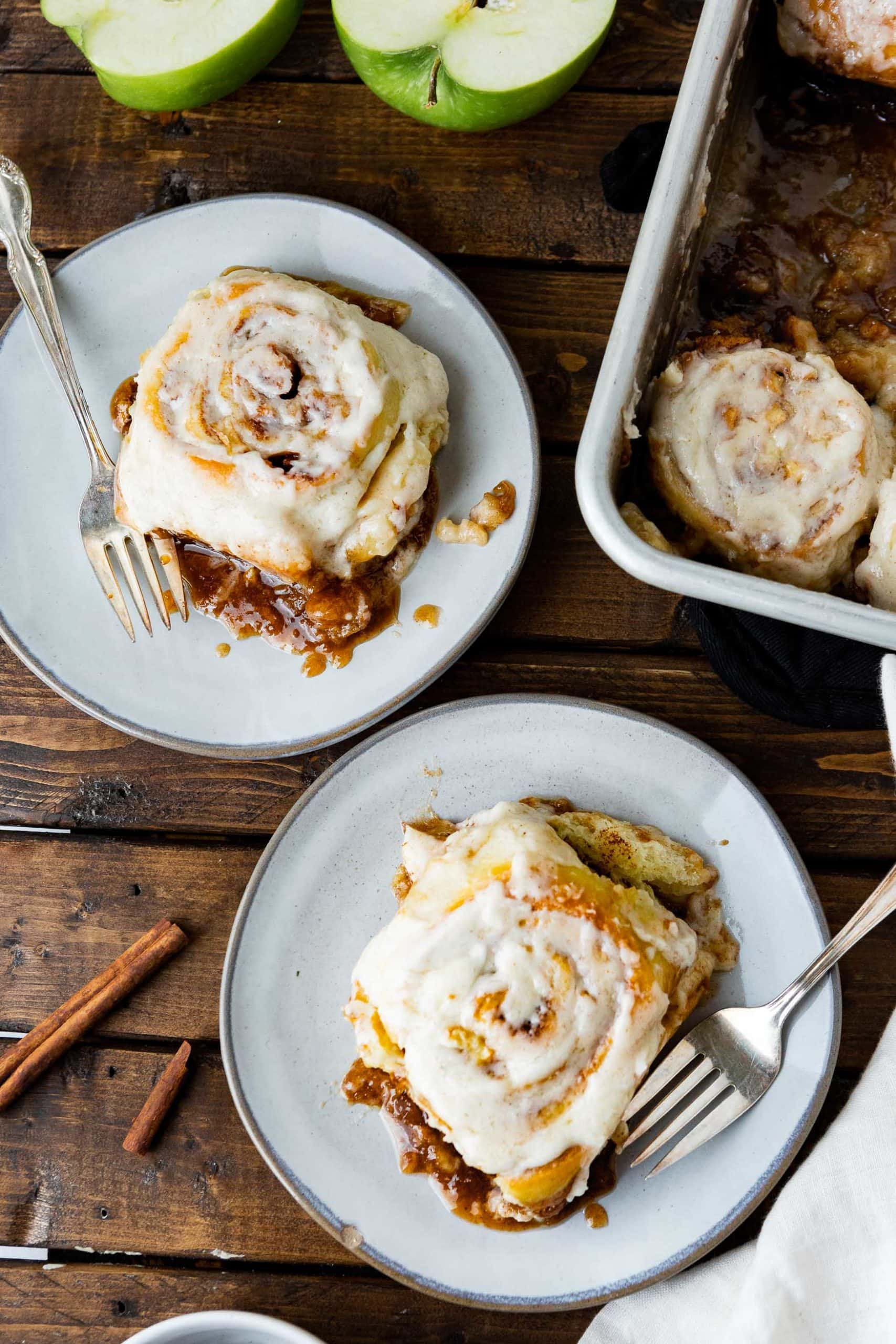 a photo of two apple cinnamon rolls each sitting on a separate saucer with a fork sitting on the saucer and covered in melty browned butter icing.