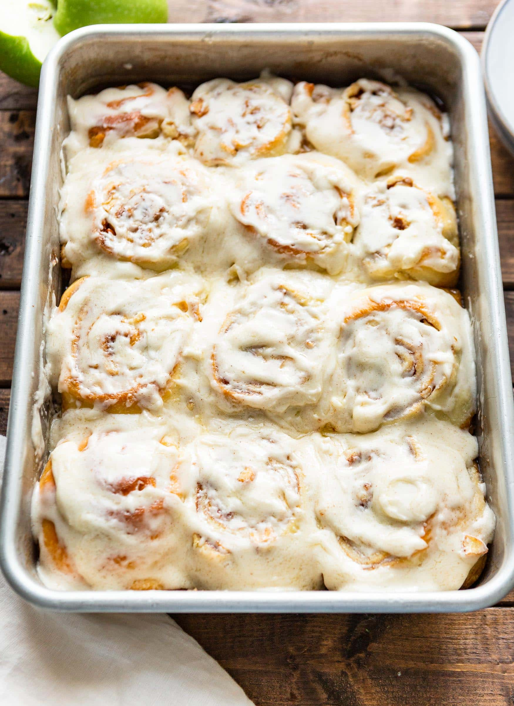a photo of a 9x13 silver pan full of frosted golden cinnamon rolls.