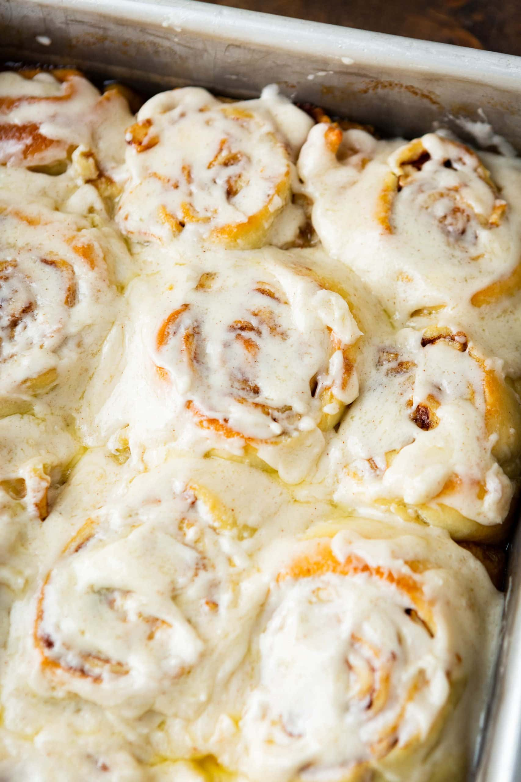 a closeup photo of a pan full of golden apple cinnamon rolls topped with melty browned butter frosting.