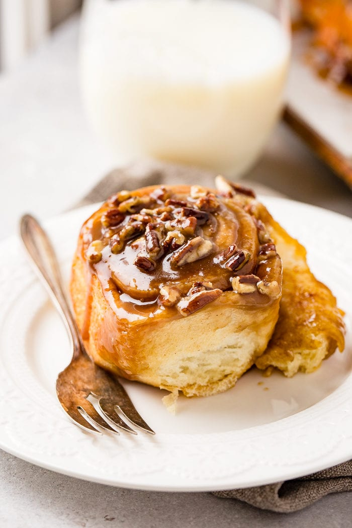 A photo of a sticky bun sitting on a white plate with a fork next to it.