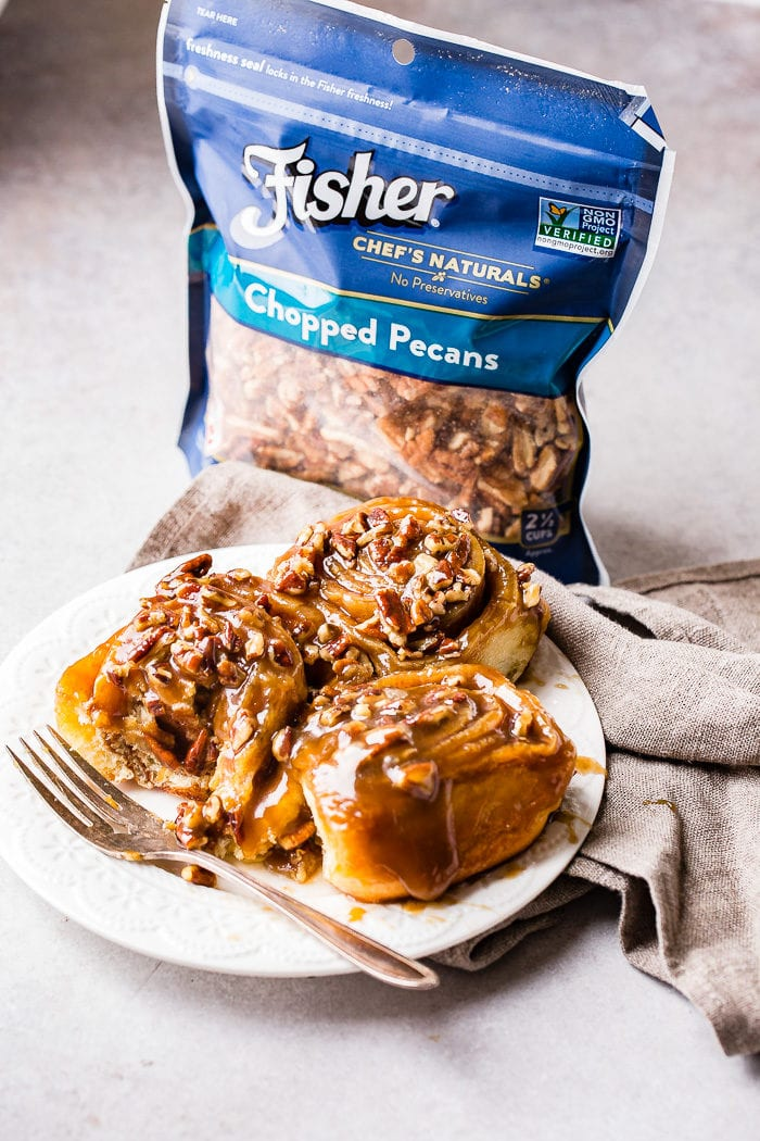 A photo of three sticky buns on a white plate with a fork sitting next to them and a bag of Fisher chopped pecans in the background.
