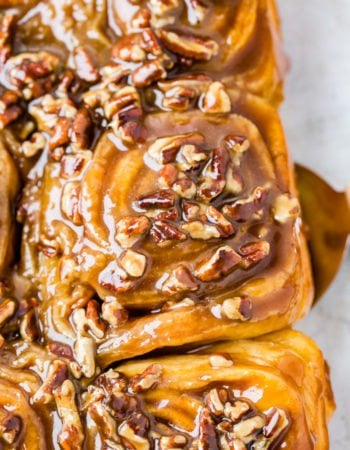 A photo of a sticky bun taking from above covered in a caramel glaze and chopped pecans.