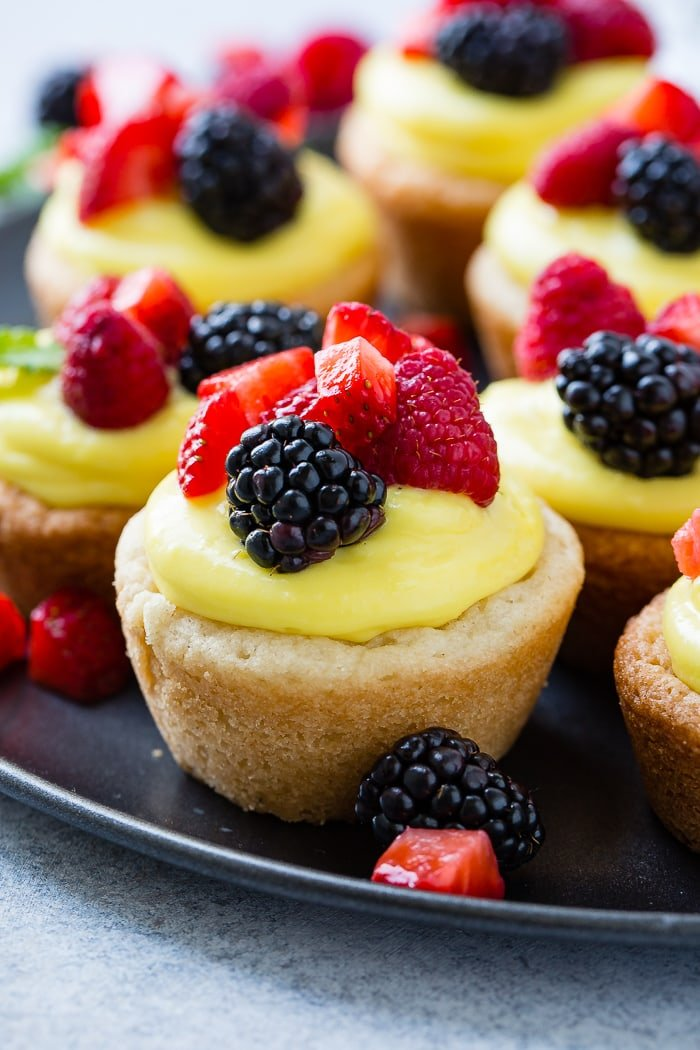 A dark pan with a close up of a sugar cookie cups filled with lemon filling and topped with blackberries, raspberries and chopped strawberries