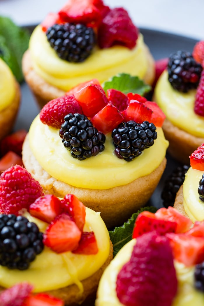 A dark pan with sugar cookie cups filled with lemon filling and topped with blackberries, raspberries and chopped strawberries