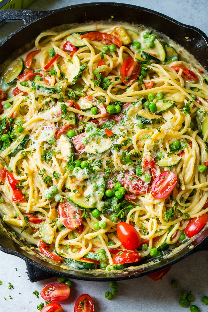 a large skillet with spaghetti pasta, zucchini, peas and tomatoes in a spicy queso sauce