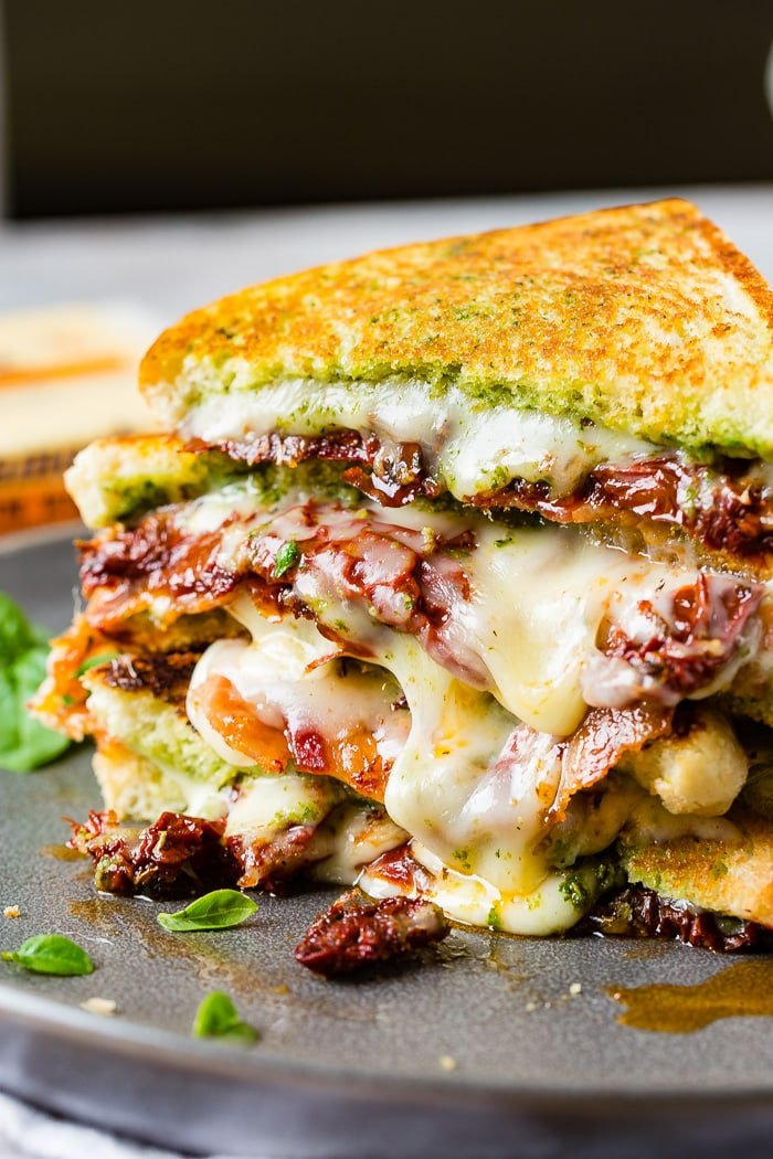 Two stacked sun dried tomato bacon pesto grilled cheese sandwiches with little basil leaves