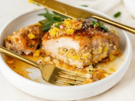 A stuffed pork chop that has been cut, exposing the stuffing inside. The pork chop is sitting in a golden sauce and a knife and fork are resting on the plate.