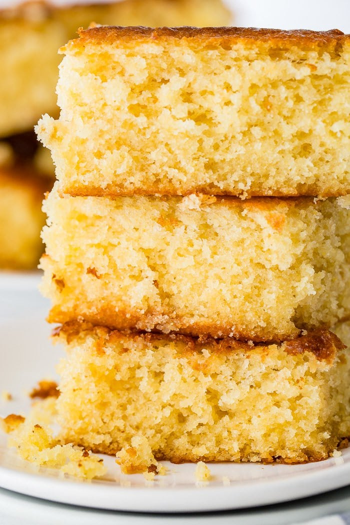 A photo of three pieces of homemade sweet cornbread stacked on top of each other.