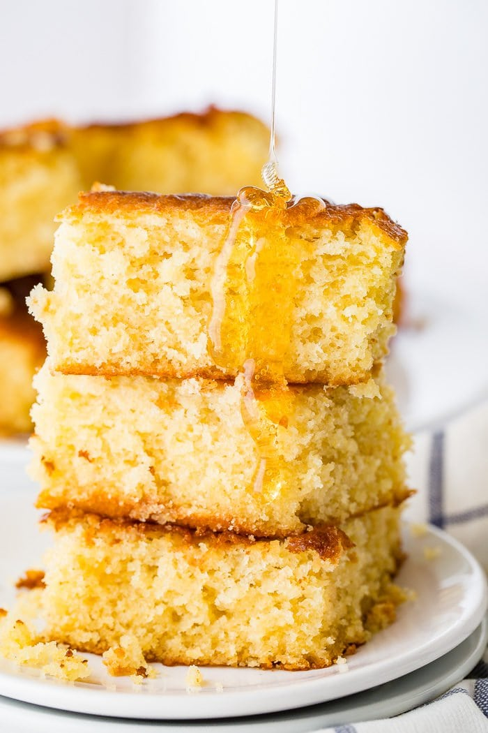 A photo of three pieces of homemade sweet cornbread stacked on top of each other with honey drizzled all over them.
