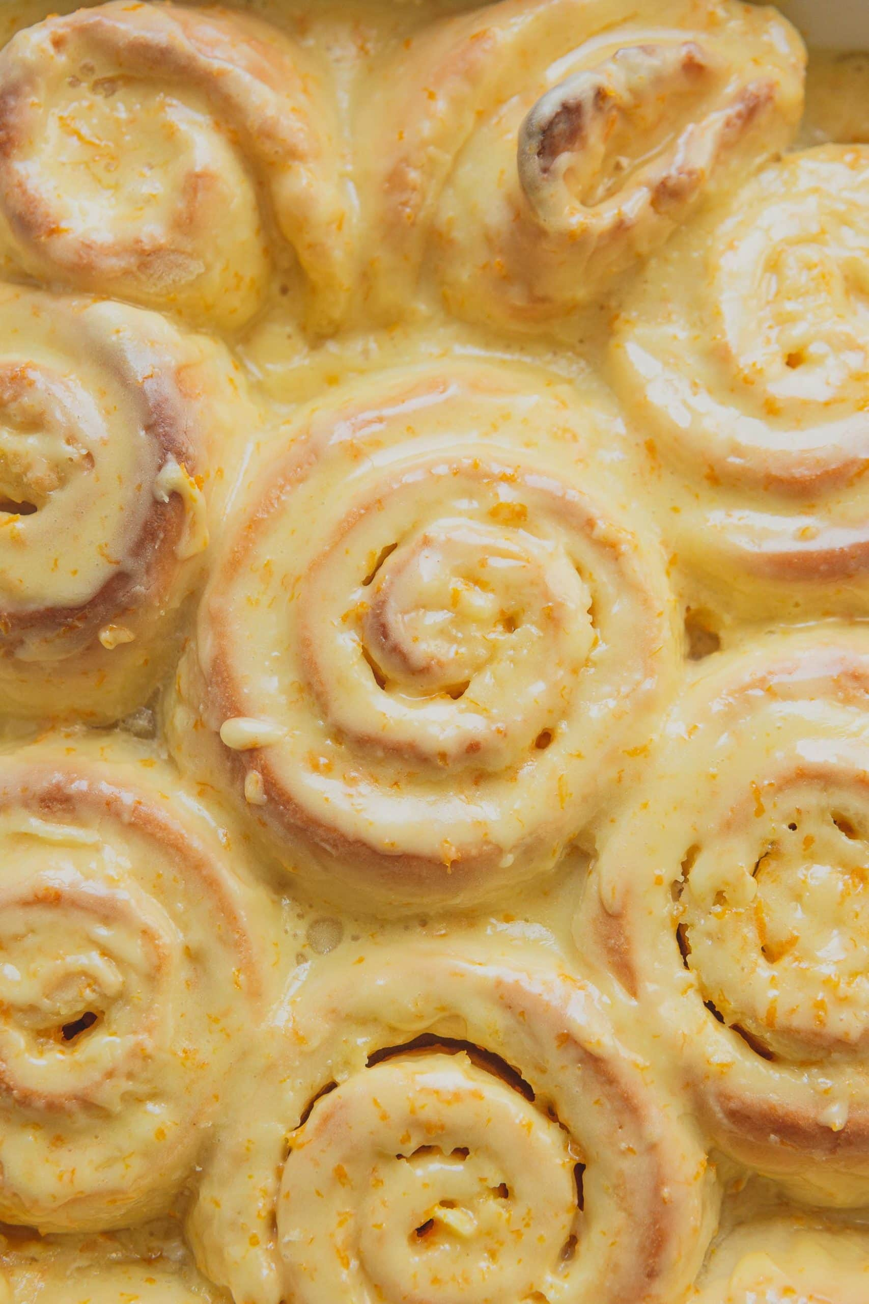 A close up, top view of a pan of orange rolls. They are topped with orange frosting.
