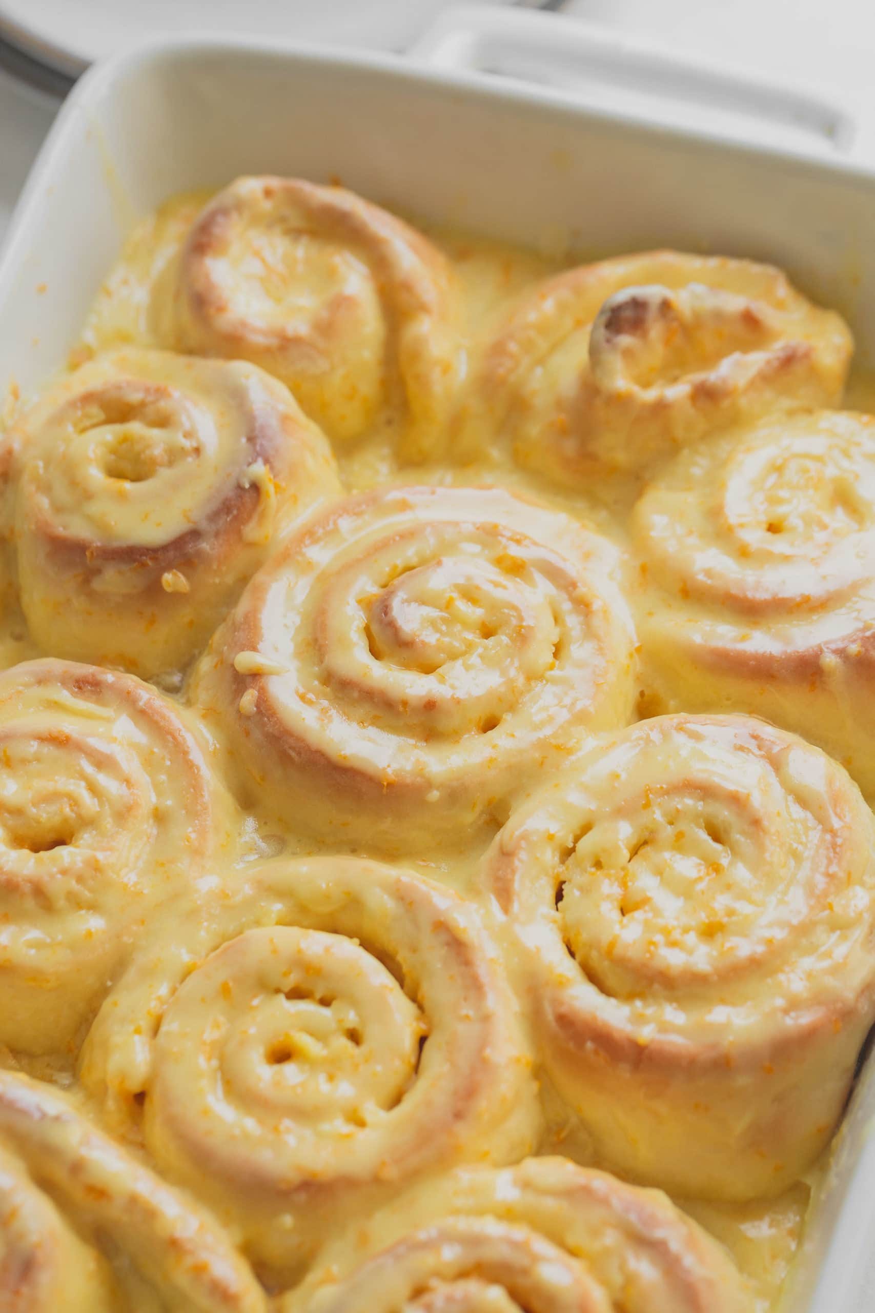 A pan of baked, glazed orange rolls. They are golden brown with an orange glaze filled with bits of orange zest.